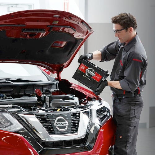 Nissan Service Technician replacing a car battery