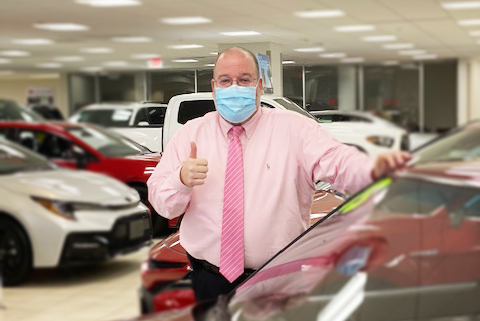 Toyota Salesman infront of Vehicle in the showroom