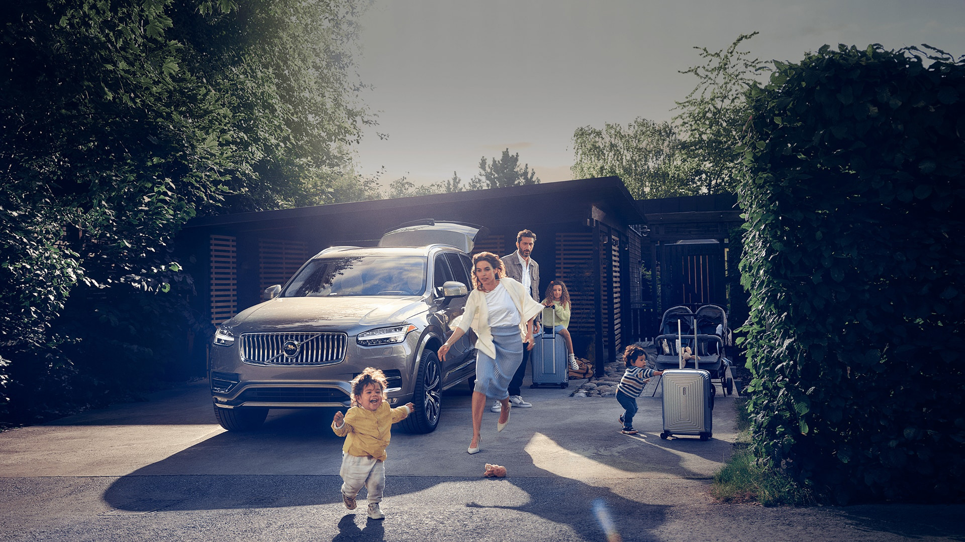 A grey Volvo XC90 SUV and a family with young children trying to pack up and leave home