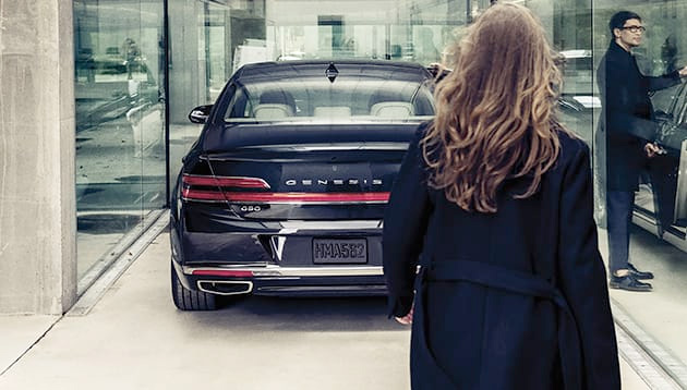 Woman walking into a Genesis showroom